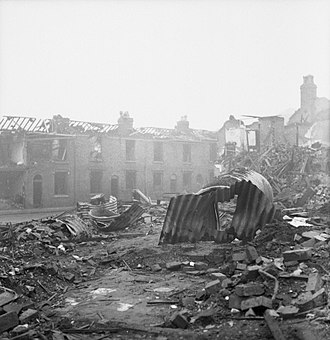 Parable of the broken window - Partly-cleared bomb damage in an industrial area. The roofless buildings are houses. The corrugated metal in front of the pile of bricks and framing timber is the remains of several air-raid shelters.