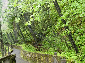 Landslide mitigation - A boulder catching net on a trail at Multnomah Falls, Oregon, USA, erected to protect hikers from debris falling down the steep incline.
