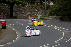 Braddan Bridge - F2 sidecar outfits showing the racing line through the 'S' bend at Braddan with machines on the actual bridge over the river, having a railed parapet to the right and wall with over-run buffers to the left