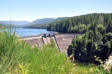 A large concrete dam impounds a lake surrounded by tree-covered hills.