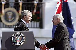 Photograph of U.S. President George W. Bush shaking hands with Australian Prime Minister John Howard, during the State Arrival Ceremony held for the Prime Minister on the South Lawn of the White House, May, 2006