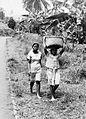 COLLECTIE TROPENMUSEUM Een man met een draagmand op het hoofd en een vrouw lopend langs de weg tussen Bogor en Sukabumi TMnr 20000021.jpg
