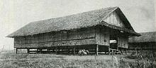 Black-and-white image a grass nipa hut raised a few feet off the ground by wooden supports. Another hut can be seen in the background.