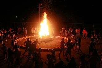 Orientation camps in Hong Kong - Students forming a circle surrounding the fire.