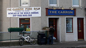 """Deep-fried Mars bar - A banner on the Carron fish shop in Stonehaven, reading """"Birthplace of the World Famous Deep Fried Mars Bar"""", December 2007"""
