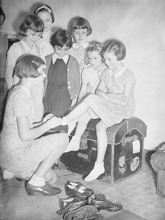 German occupation of the Channel Islands - 1940: A group of girls evacuated from the Channel Islands to Marple in Cheshire try on clothes and shoes which have been donated by the United States.