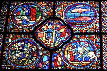 Part of a large window. It is divided into four circular panels with a quatrefoil (or four-lobed section) between them and an arched segment beneath. To the lower right, a knight, Sagittarius, is being welcomed home. At the centre a man empties a water pot, symbolising Aquarius and a two-faced figure symbolises New Year. To the upper right, are the two fish of Pisces. The other sections show each month's activities: grapevine pruning, bell-ringing and sitting by the fire.