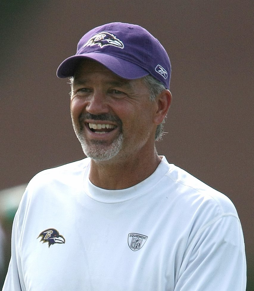 Color head-and-shoulders photograph of well-tanned, smiling white man with salt-and-pepper goatee (Chuck Pagano), wearing a white crewneck shirt and purple baseball cap, both emblazoned with Baltimore Ravens logos.