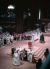 Intérieur d'une église remplie de personnes en robes et en uniformes de cérémonie. Un trône a été placé sur un piédestal au centre de l'image et la reine avec une longue traine rouge se tient à proximité.
