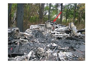 Corporate Airlines Flight 5966 - Photograph of main wreckage area. The forward section of the airplane is in the foreground, and the tail section is in the background (the aft pressure bulkhead is indicated by the red arrow)