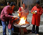 An Indian family performing a religious ritual over a fire.