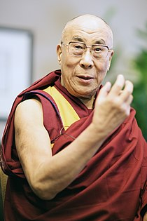 Gyatso dressed in robes raising his hands