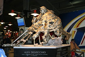 "A large bronze statue of an ice hockey player in the act of shooting the puck.  The player's hands and stick are shown numerous times in order to simulate motion. At the base of the statue is inscribed ""Alex Delvecchio Born: December 4, 1931 Fort William, Ontario, Canada"