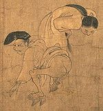 A man suffering from diarrhea squatting with a woman watching his back.