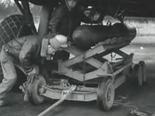 Photograph of three men using lifting equipment to jack a heavy bomb up to the underside of a large parked aircraft