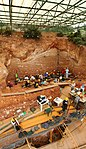 Archaeological excavation site in red earth.