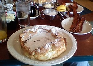 Dutch baby pancake - A Dutch Baby served with lemon slices, powdered sugar, butter, and a side of bacon
