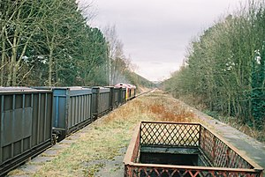 East Leake railway station - A train of empty gypsum containers passes through the disused East Leake station
