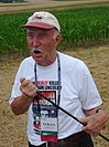 Man in a ball camp and white Tshirt holding a thin rod and standing in a field