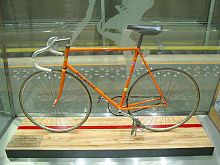 An orange bicycle behind glass.