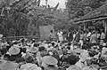 Een KNIL-militair spreekt met een man in witte kleding. Achter hem een schoolbor, Bestanddeelnr 446-1-4.jpg