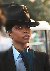 An image of a woman with a fedora and a suit holding blue feathers while staring forward with a neutral expression