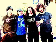Fall Out Boy standing still while posing for a camera.