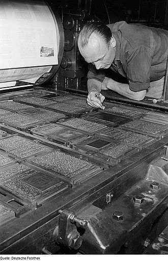 Letterpress printing - A printer inspecting a large forme of type on a cylinder press. Each of the islands of text represents a single page, the darker blocks are images. The whole bed of type is printed on a single sheet of paper, which is then folded and cut to form many individual pages of a book.