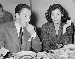 A man and woman sit next to each other at a table. The man eats while the woman smokes a cigarette.