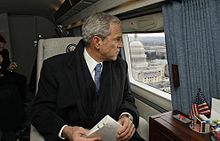 George W. Bush wearing a suit, tie, scarf and overcoat while looking out the window from a skyward vehicle.