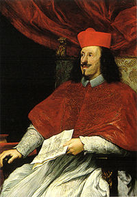 A black-haired, bearded man in his mid-thirties wears the garb of a Roman Catholic cardinal.