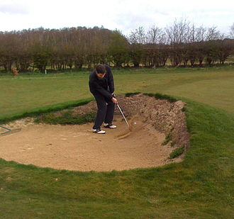 Hazard (golf) - A golfer hitting from a greenside bunker