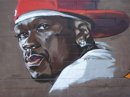 "Graffiti depicting US rapper 50 Cent. Larry Nager of The Cincinnati Enquirer wrote that 50 Cent has ""earned the right to use the trappings of gangsta rap - the macho posturing, the guns, the drugs, the big cars and magnums of champagne. He's not a poseur pretending to be a gangsta; he's the real thing."" Graffiti of 50 Cent.jpg"