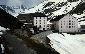 Great St Bernard Pass - Hospice at the Great St Bernard, with Roman road in foreground. The modern road is below it. To the right the snowy slope descends to the tarn. On the other side of the monastery buildings the road descends into Switzerland.
