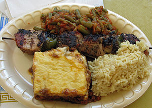 Yahni - Plate of Greek food - yahni at top center, with pork souvlaki immediately below, mousaka (bottom left) and rice pilaf (bottom right)