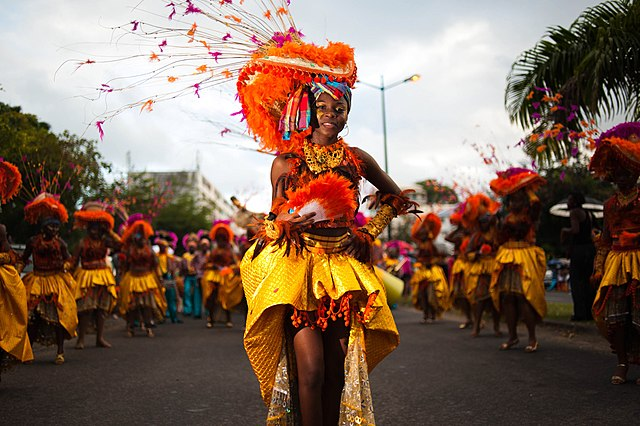 https://upload.wikimedia.org/wikipedia/commons/thumb/3/30/Guadeloupe_winter_carnival,_Pointe-%C3%A0-Pitre_parade._A_young_woman,_performer_wearing_traditional_carnival_outfit_(waist_up_outdoor_portrait)-3.jpg/640px-Guadeloupe_winter_carnival,_Pointe-%C3%A0-Pitre_parade._A_young_woman,_performer_wearing_traditional_carnival_outfit_(waist_up_outdoor_portrait)-3.jpg