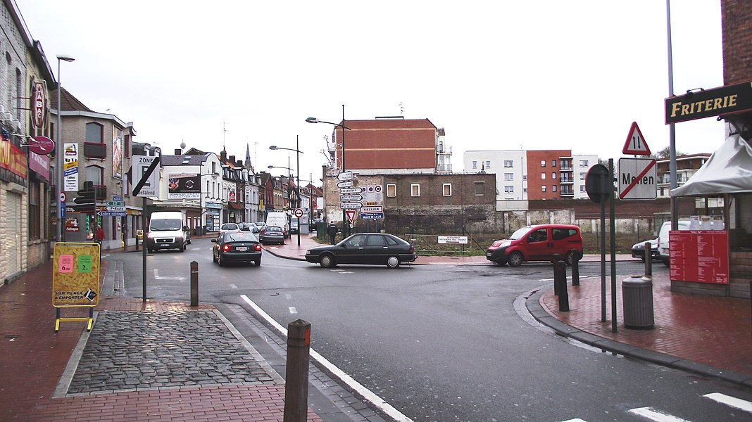 Border between France and Belgium in the border towns of Halluin (France) and Menen (Belgium). View from the Belgian side. The empty right corner of the crossing is French (The buildings have been demolished in 2010, zie GE). Beyond the white building (behind white van) on the second crossing is also French. Language on signs is strictly dependent on where the sign is situated.