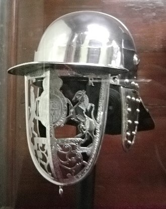 Lobster-tailed pot helmet - Modern reproduction of a helmet of James II of England made in 1686. The face protection is in the form of an openwork depiction of the royal coat-of-arms