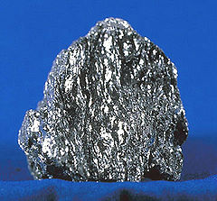 A sparkling, metallic gray chunk of hematite on a blue background.