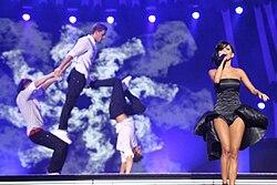 Une photographie d'Inna jouant dans une robe noire accompagnée de trois danseurs de secours.