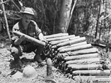 A soldier kneels beside a pile of artillery shells in a clearing in the jungle, closely inspecting one that he is holding