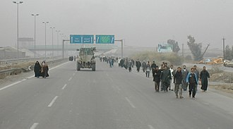 January 2005 Iraqi parliamentary election - With civilian cars banned from roads for security, hundreds of residents of the Al Monsour district of Baghdad walk along a freeway to the polls.