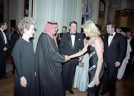 King Fahd with U.S. President Ronald Reagan and future U.S. President Donald Trump in 1985. The U.S. and Saudi Arabia supplied money and arms to the anti-Soviet mujahideen fighters in Afghanistan. Ivana Trump shakes hands with Fahd of Saudi Arabia.jpg
