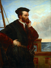 A bearded explorer dressed in dark velvet with a sheathed sword and a hat. He is on a ship and looks out towards the sea