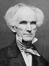 A daguerrotype of an elderly man with startling white curly hair standing out from both sides of his head.