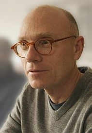 A bald man wearing glasses and a gray T-shirt looks off-screen.