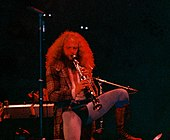Jethro Tull leader Ian Anderson, wearing a codpiece and tights, stands on one leg as he plays a soprano saxophone