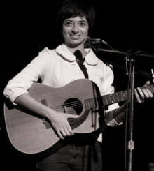 Micucci on stage at microphone, holding guitar, with her trademark bob hairstyle, wearing a bright big-buttoned midi-sleeve blouse