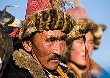 Photo montrant le visage d'un homme avec un chapeau de fourrure et de plumes; un autre homme est visible à l'arrière-plan, en flou.