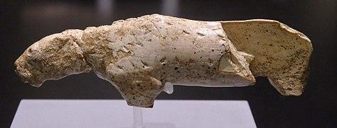 Photographie en couleurs et de profil d'une statuette en ivoire représentant un léopard des neiges, le corps fixé sur un axe en verre, l'échine marquée d'incise, la gueule entrouverte et au flanc postérieur gauche disparu.